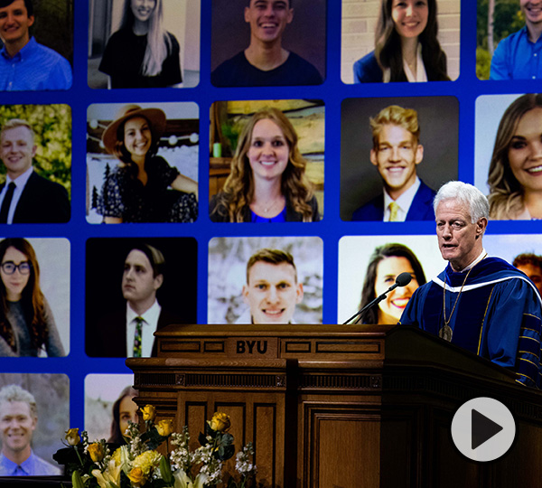 President Kevin Worthen speaks at the Marriott Center podium in front of a video display of graduates he  qualified as super because they were resilient, durable, and adaptable throughout a global pandemic.