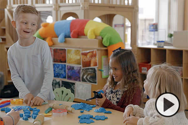 Three young children play with blue play dough at a table in the BYU Child and Family Studies Lab.