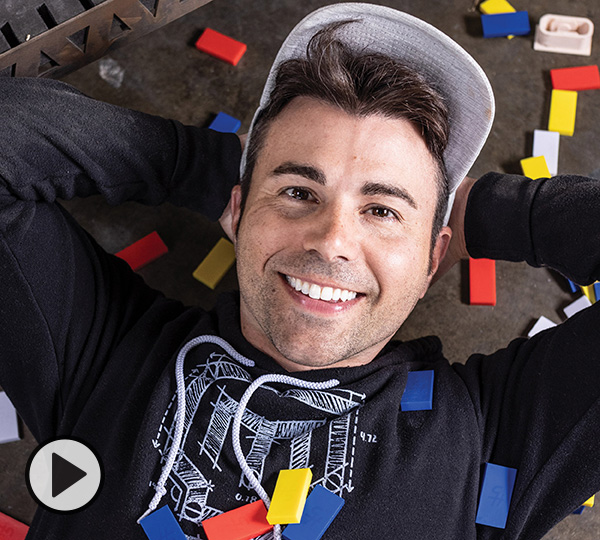 YouTuber Mark Rober, hands behind his head, is laying down on his workspace floor surrounded by yellow, red, white, and blue dominos.