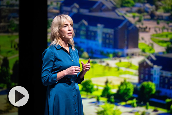 During her recent BYU devotional, Lisa Valentine Clark stands and speaks in front of giant monitors displaying campus scenes.