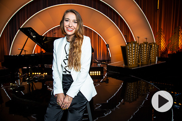 Singer Lauren Daigle smiles in front of a stage with a curtain, music stands, and circular amber lighting.