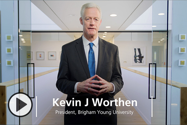 Kevin J Worthen, President, Brigham Young University, is framed by glass doors and white walls.