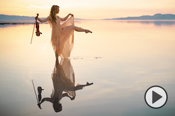 Standing in the water of the Great Salt Lake, Lindsey Stirling holds her violin behind her as she  strikes a reflective pose.