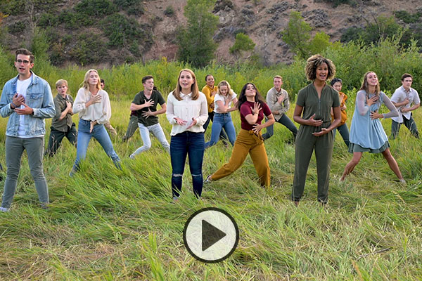 BYU's Young Ambassadors dance and sing in a grassy field.