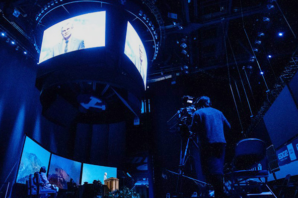 A speaker, multiple screens, and the LED board, along with all of the elements of a BYU devotional being held in Marriott Center. A TV camera is shown in the foreground.
