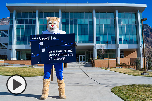 Standing in front of the Engineering Building, Cosmo holds a sign that reads BYU engineering Rube Goldberg Challenge.