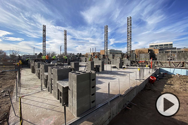 Concrete, rebar, and cinder blocks are visible in this image of the Music Building construction, backed by a dramatic blue sky with wispy clouds.