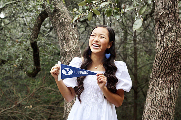 New BYU student Hannah Larson is wearing a large blue heart earring and a huge smile as she stands in a wooded area, holding a blue and white Y Cougars banner. Photo by Kelly J. Larson.