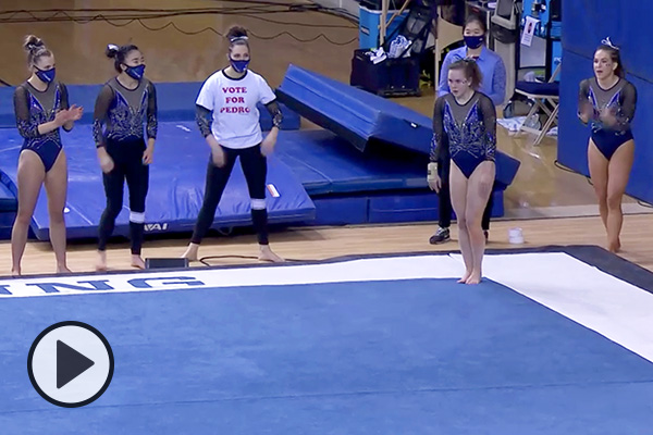 BYU gymnast Jordan Matthews prepares to make a tumbling pass during a floor routine. Nearby a teammate wears a Vote for Pedro T-shirt.