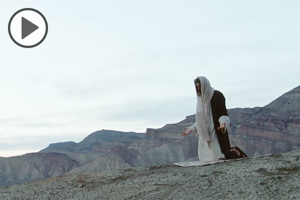 An actor portraying Jesus Christ kneels on a slope overlooking a mountainous desert.