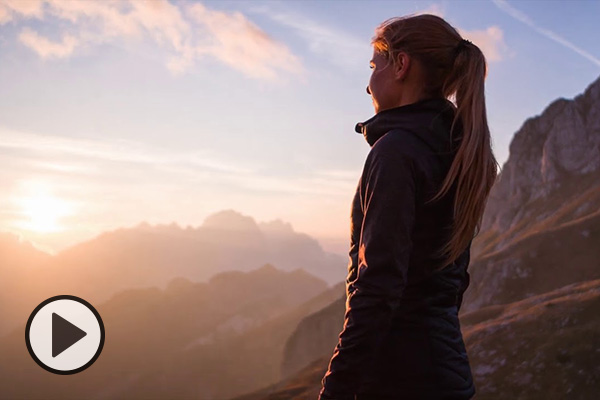 A young woman in an athletic jacket looks at mountains on the horizon.