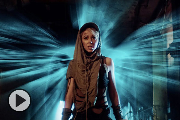 Wearing Mad Max-style futuristic garb, Lindsey Stirling is bathed in a wave of cyan-blue ethereal light.