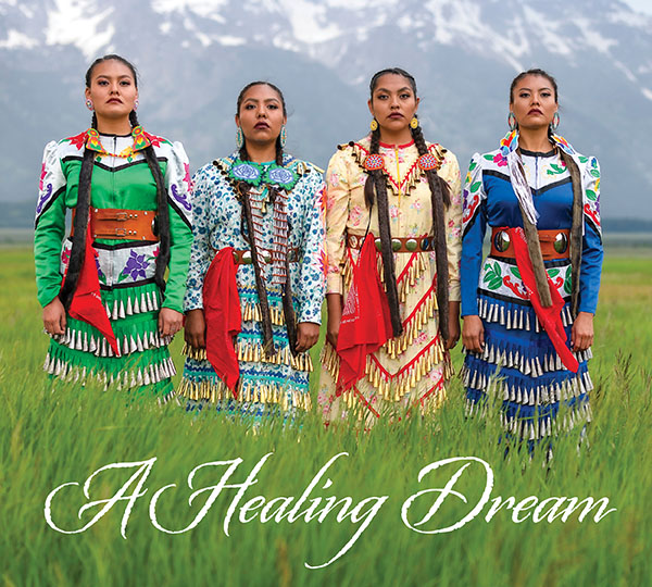 A Healing Dream is the text that accompanies an image of four jingle dress dancers standing in tall grass in front of the Grand Tetons.