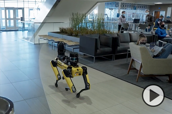 A robotic dog patrols the hallways of BYU's Engineering Building, catching the attention of students in a study or lounge area.