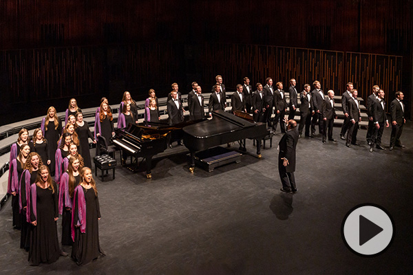 BYU Singers perform in a U-shaped formation surrounding two pianos and the choir director.