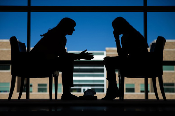 Two sihouetted women sit in facing chairs to illustrate research from BYU professors Timothy Smith and Julianne Holt-Lunstad that found that interpersonal relationships are key parts of medical treatment plans and help patients reduce stress and live longer.