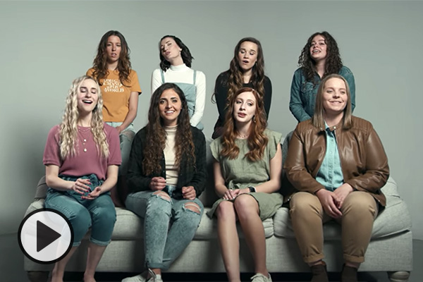 Eight female singers on a couch.