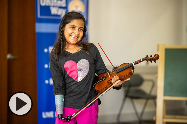 Adia Cardona, a 10-year-old violinist, with her prosthetic limb and a recently engineered device.