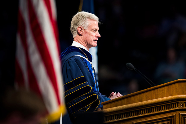Wearing blue and gold graduation robes, President Kevin J Worthen stands at the Marriott Center podium, a US flag in the foreground.