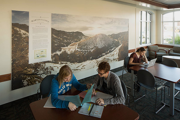 Three students study at tables in front of a mural of Martin's Cove in BYU's Heritage Halls.