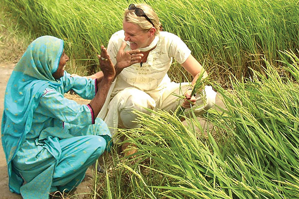 Tiffany Ivins Spence visits with a Pakistani woman near a field with green stalks.