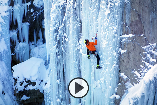 A climber in an orange jacket uses ice climbing gear to ascend a frozen waterfall.