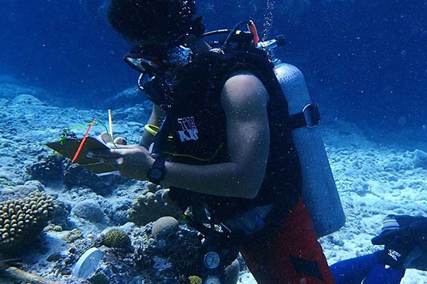 Samoan scientist Stau Segi is underwater wearing scuba gear and taking notes near a coral reef.