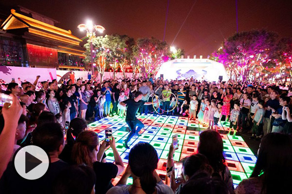 A hoop dancer performs in a public space in China at night. He is surrounded by a crowd taking pictures and cheering.