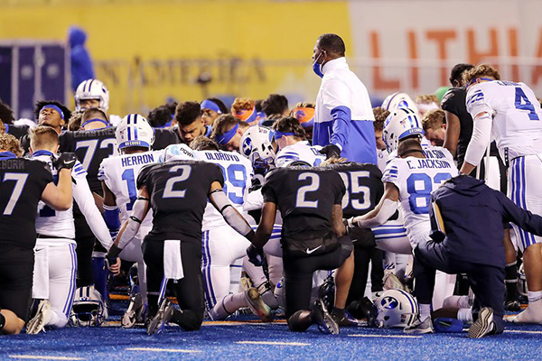 BYU and BSU players kneel together on the blue turf in Boise.