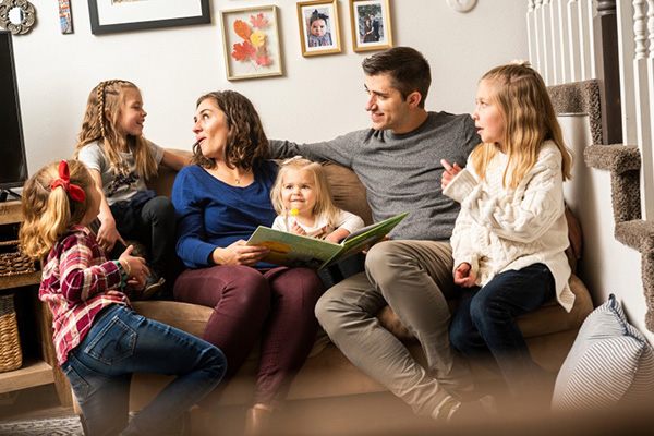 A family gathers on a couch to read a picture book and spend time together.