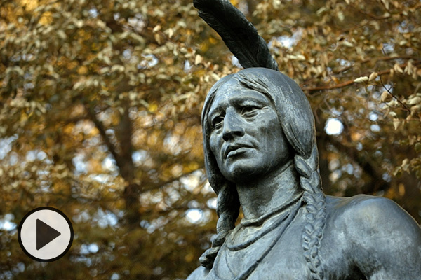 Detail of a BYU campus sculpture of Chief Massasoit, fall leaves in the background.