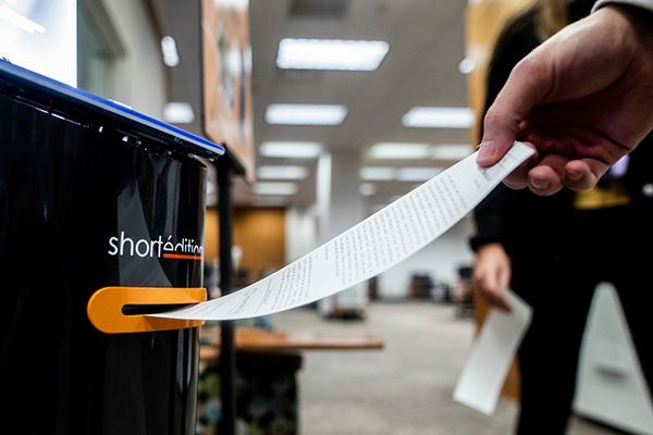 A story on receipt paper is pulled from a dispenser in the BYU library.