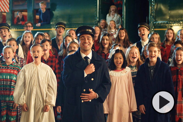 BYU Vocal Point singers in railroad attire join with a children's choir in Christmas pajamas.