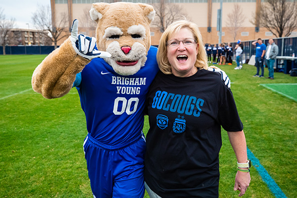 Caroline Billings and Cosmo cheer during a women's soccer game.