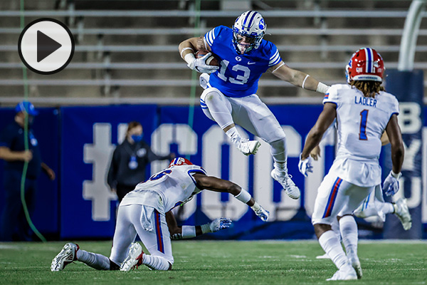 A BYU football player leaps over a defender.