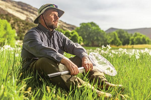 Jim Spencer sitting in a sunlit, grassy mountain meadow, butterfly net in hand.