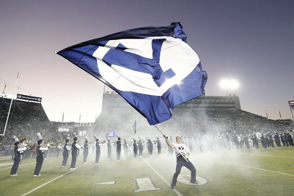 In a cloud of white smoke, a male BYU cheerleader waves a Y Flag on the football field in front of a line of marching band members.