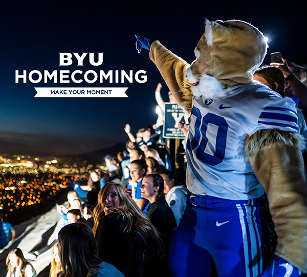 BYU Homecoming Make Your Moment. Cosmo the Cougar points to Provo from the Y on the mountain, surrounded by a group of smiling students.