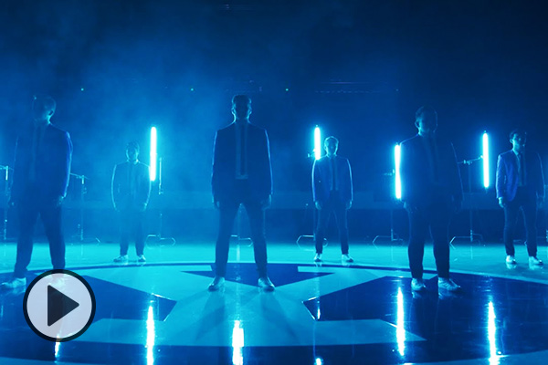 Bathed in blue light and wearing blue suits and ties, BYU Vocal Point members stands socially distanced on a high-gloss wooden playing floor, a Y logo at center.
