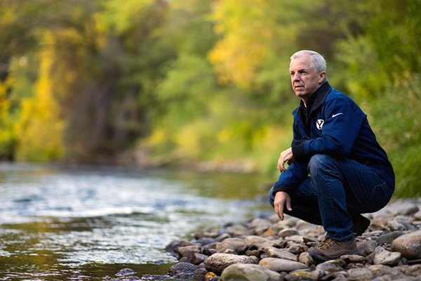 Jim Nelson, dressed all in blue, crouches on rocks near a gently flowing river.