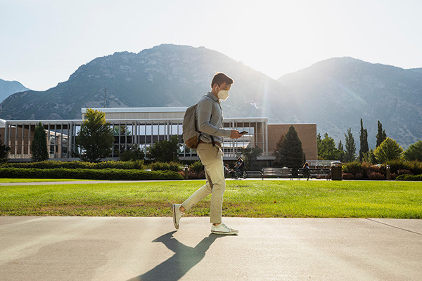 A mask-wearing student strolls on the BYU campus as the sun rises over Y Mountain.