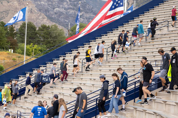 Participants in a Sept. 11 tribute at the stadium trek up and down the stairs. Both a BYU and a U.S. flag wave in the background. Photo by Jaren Wilkey.