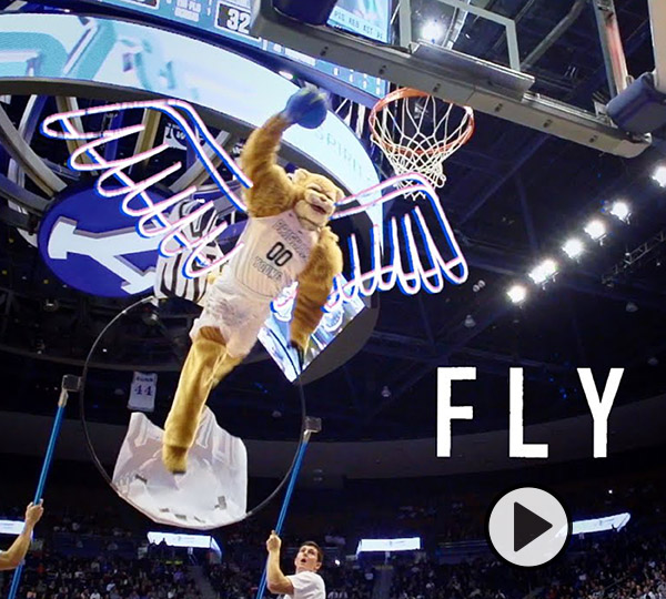 Cosmo sprouts animated wings, soars above the Marriott Center rim, and prepares to dunk a blue basketball.