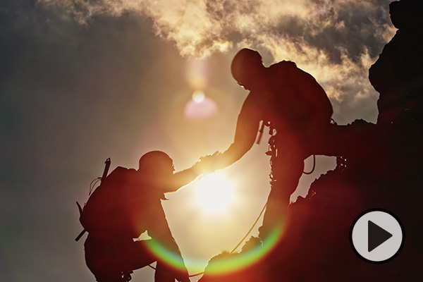A climber extends a hand to another below him on a craggy, sunlit cliff.